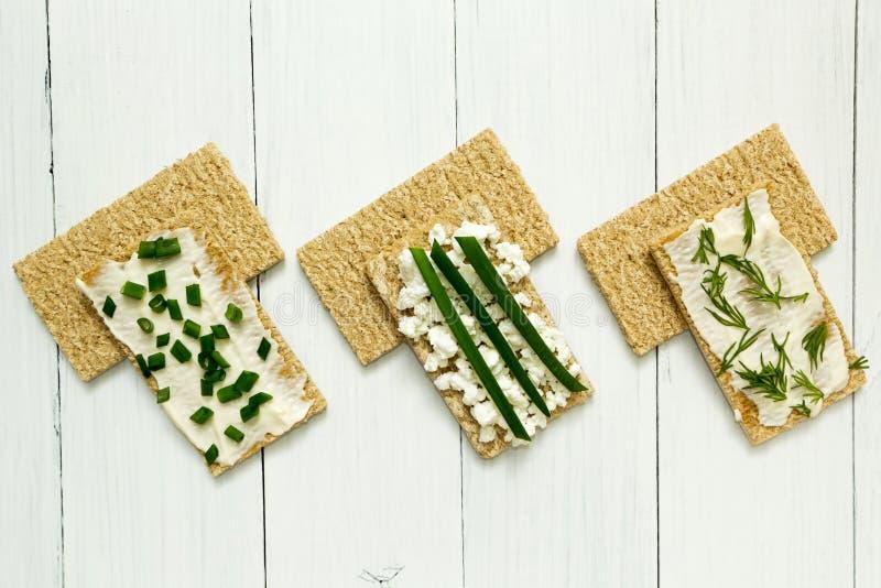 Trois petits d?jeuners v?g?tariens, pain grill?, fromage blanc, oignons et aneth sur une table en bois blanche, r?gime images stock