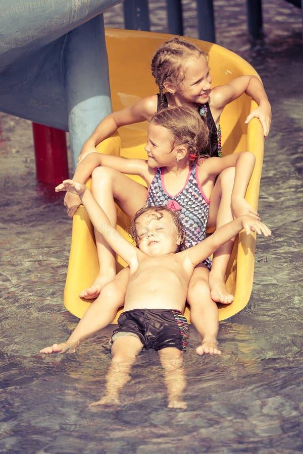 Trois petits enfants jouant dans la piscine sur la glissière image stock