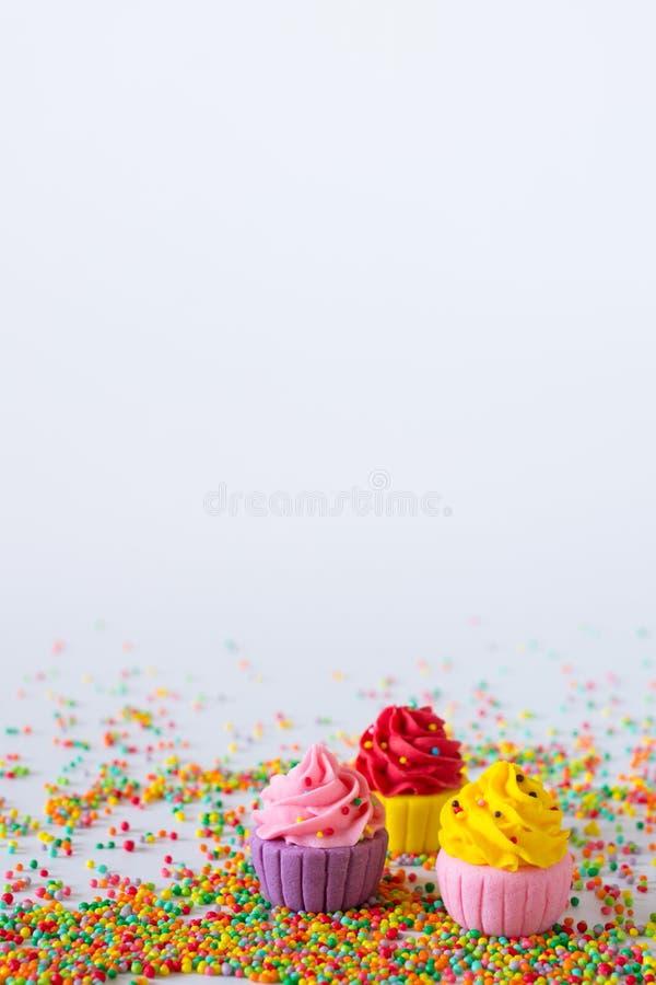 Trois petits gâteaux multicolores miniatures de sucre sur le fond clair photographie stock libre de droits