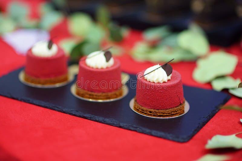 Trois petits gâteaux rouges délicieux de velours sur la table de dessert photographie stock libre de droits
