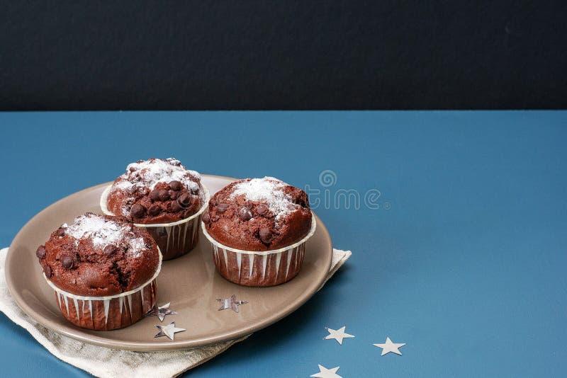 Trois petits pains de chocolat se trouvent d'un plat dans la perspective d'une table de couleur turquoise c?l?bration Anniversair image stock