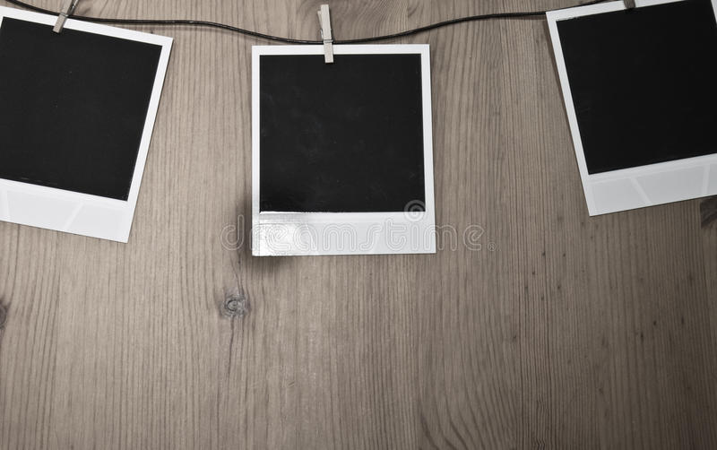 Trois photos instantanées en blanc accrochant sur la corde à linge sur le fond en bois, concept d'art image stock