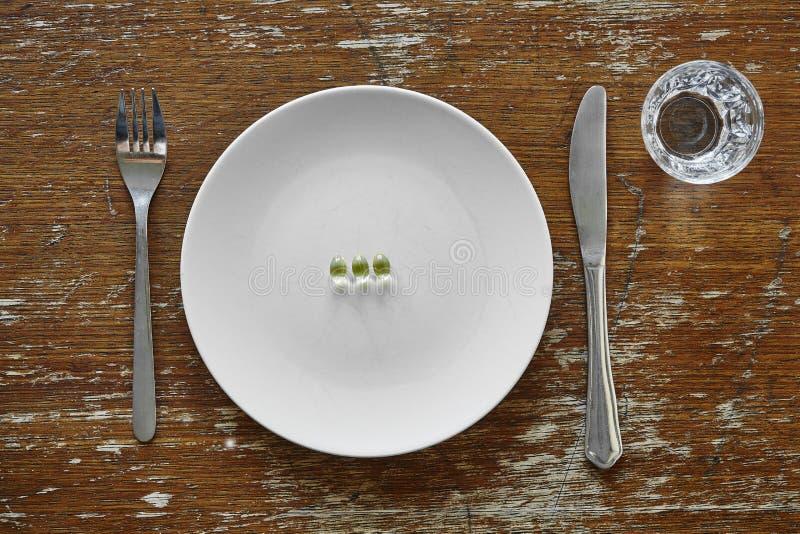 Trois pilules sur le supplément de nutrition de plat image stock