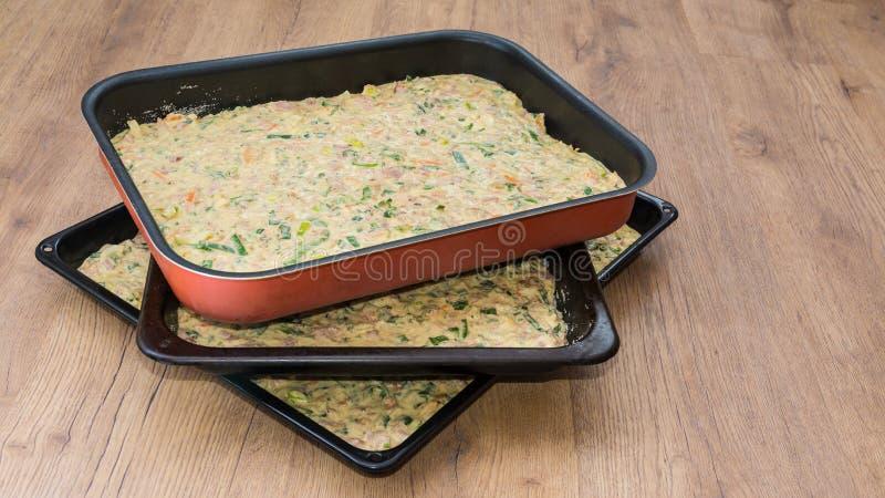 Trois plaques de cuisson avec la pâte sur le fond en bois photos stock