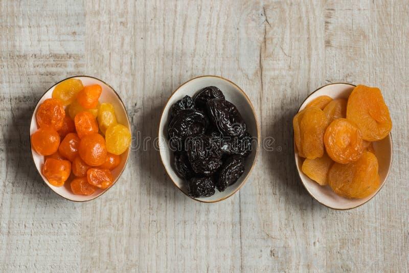 Trois plats avec les fruits secs sur le fond en bois : mandarines sèches, pruneaux et abricots secs photo libre de droits