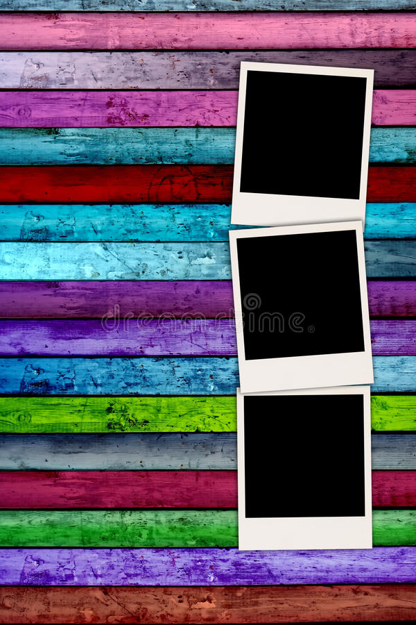 Trois polaroïds en blanc sur le fond en bois coloré photographie stock libre de droits