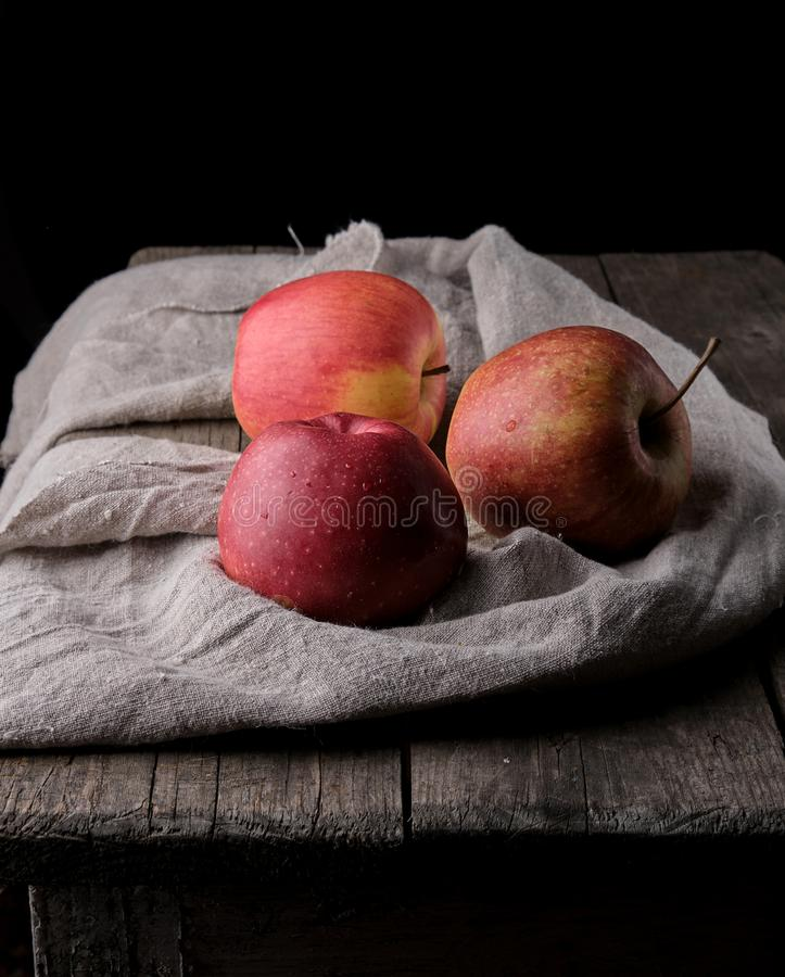 trois pommes rouges fraîches s'étendent sur la serviette de toile grise images libres de droits