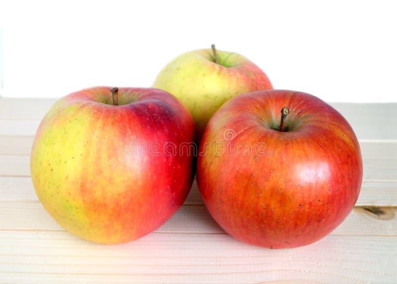 Trois pommes rouges mûres en plan rapproché en bois beige d'étagère photos libres de droits