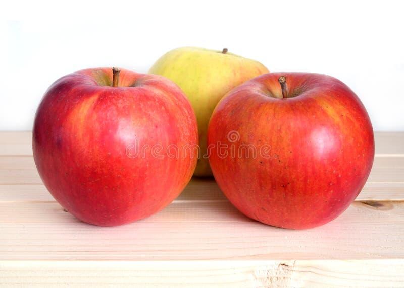 Trois pommes rouges mûres en plan rapproché en bois beige d'étagère images libres de droits
