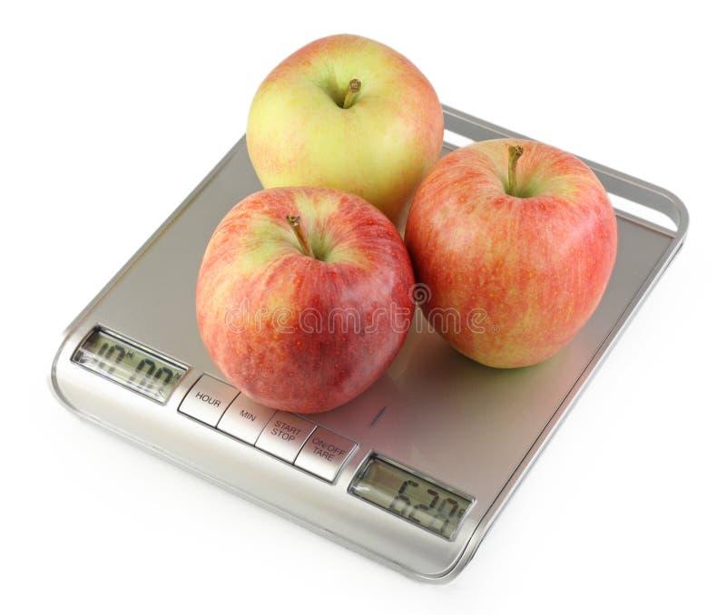 Trois pommes sur l'échelle de cuisine photographie stock libre de droits