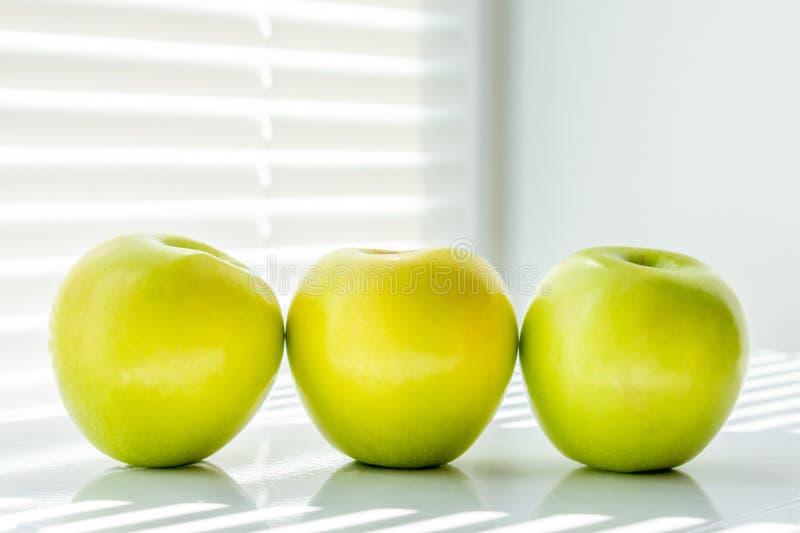 Trois pommes vertes dans une rang?e photographie stock libre de droits
