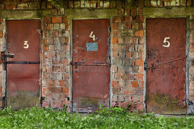 Trois portes en acier minables, rouge peint sur un entrepôt abandonné photographie stock