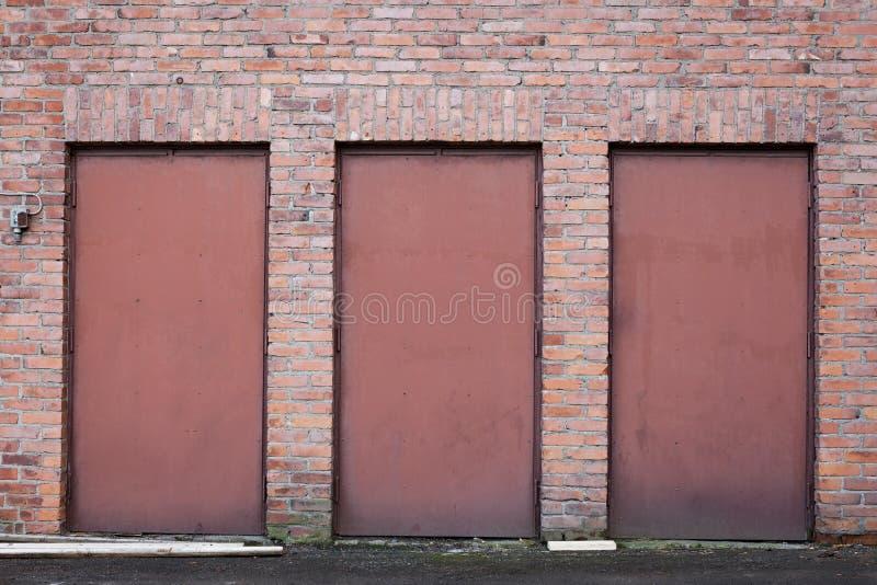 Trois portes rouges en métal dans le mur de briques photographie stock