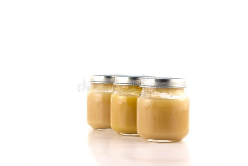 Trois pots avec la purée de fruit dans photo stock
