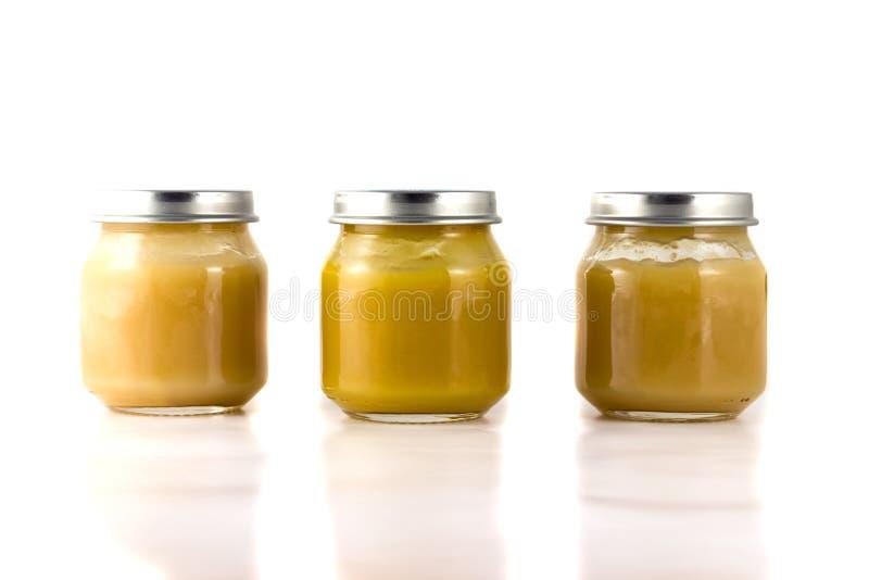 Trois pots de purée de fruit dans une rangée photos libres de droits