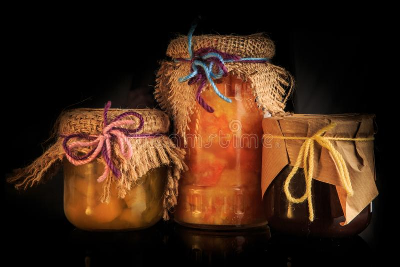 trois pots en verre de confiture faite maison savoureuse avec la décoration rustique photos libres de droits