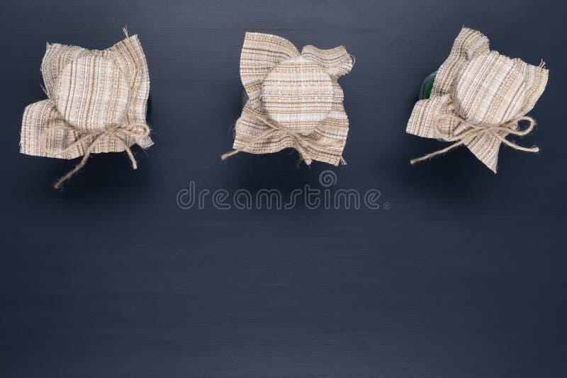 Trois pots se sont fermés avec un tissu sur un noir image libre de droits