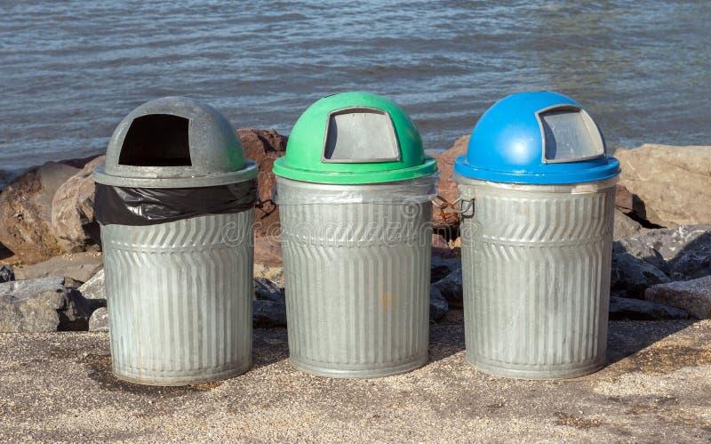 Trois poubelles publiques (réutilisez les poubelles) près de la rivière image libre de droits