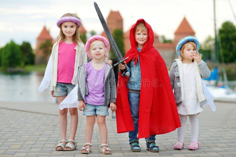 Trois princesses et un chevalier ayant l'amusement dehors photo stock