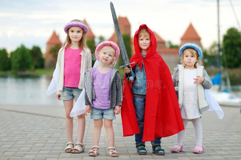Trois princesses et un chevalier ayant l'amusement dehors images stock