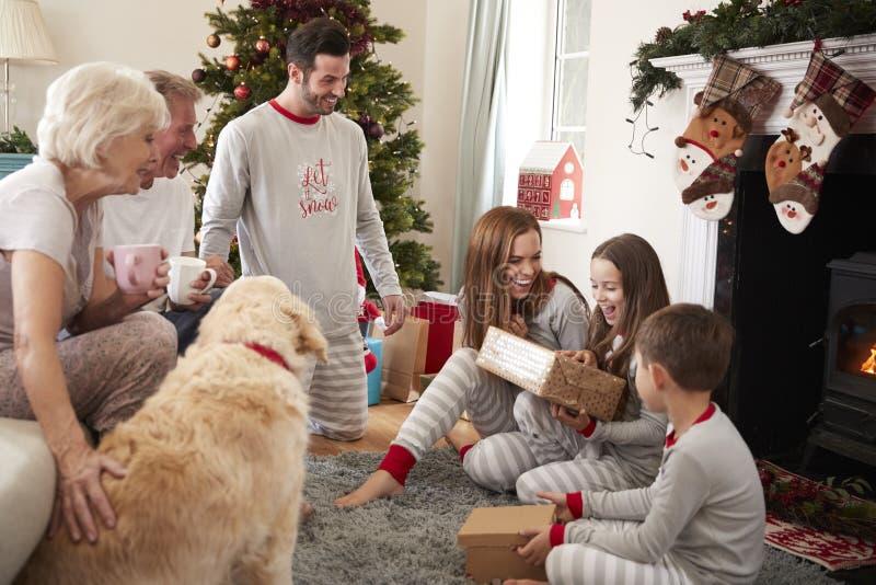 Trois pyjamas de port de famille de génération dans le salon à la maison ouvrant des cadeaux le jour de Noël photos stock