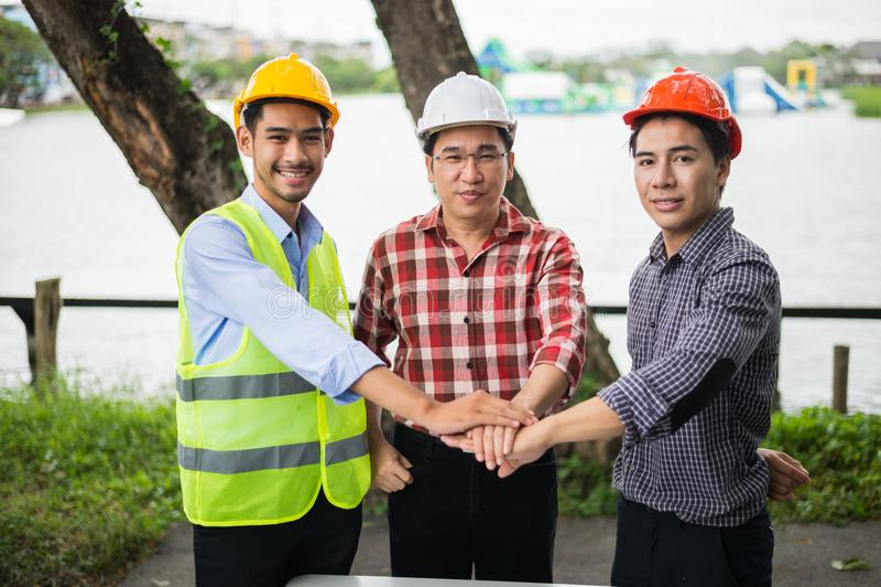 Trois que la main des ingénieurs prennent la coordination pour concluent un accord dans l'investissement au sujet de la maison et photos stock