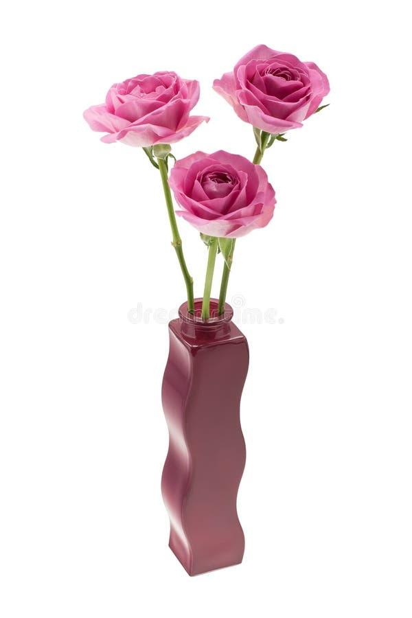 Trois roses roses dans un vase onduleux photographie stock