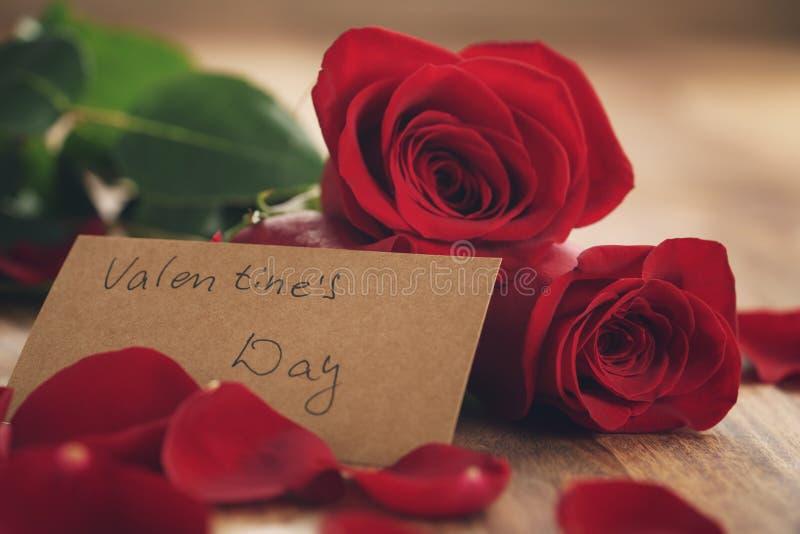 Trois roses rouges et pétales sur la vieille table en bois avec la carte de papier pour le jour de valentines photographie stock libre de droits