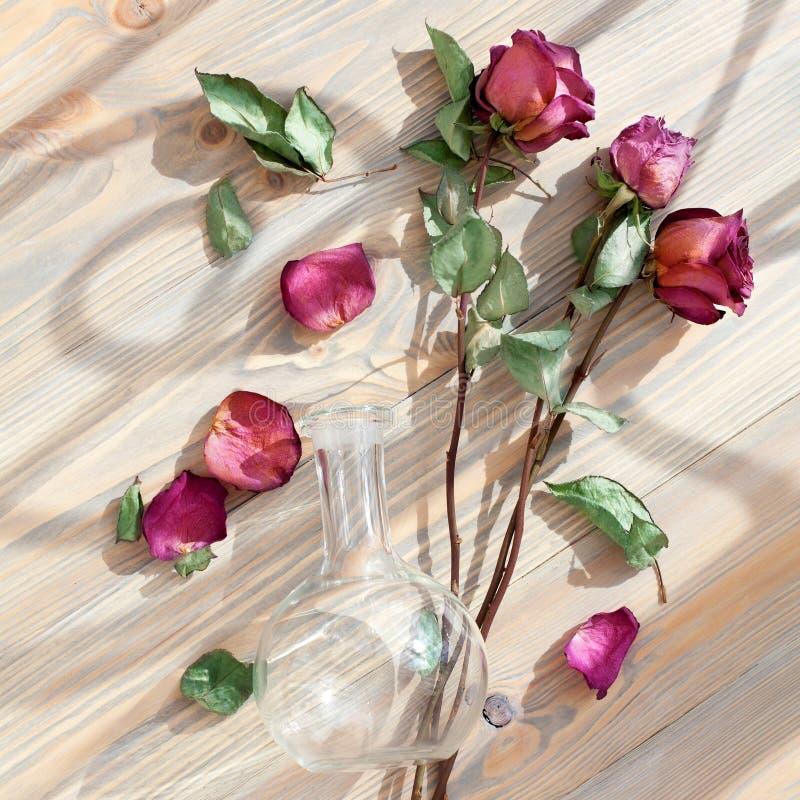 Trois roses rouges, p?tales dispers?s de fleur, feuilles vertes, vase rond en verre sur le plan rapproch? en bois de vue sup?rieu photo libre de droits