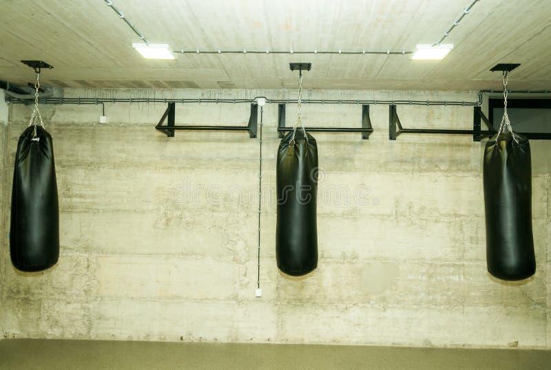 Trois sacs de sable noirs dans le gymnase vide de boxe avec le mur grunge nu à l'arrière-plan image libre de droits