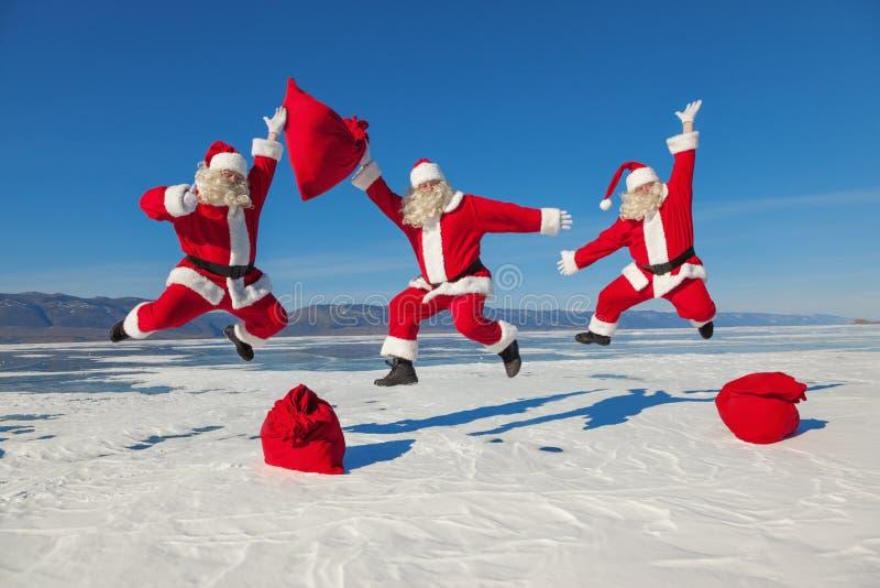 Trois Santa Claus sautante dehors images stock