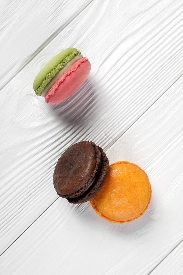Trois saveurs françaises différentes de macarons sur la vue supérieure de fond en bois image libre de droits