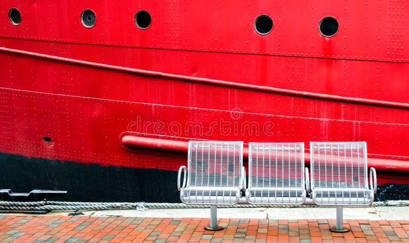 Trois sièges vides sur un quai à côté d'un grand bateau rouge images libres de droits