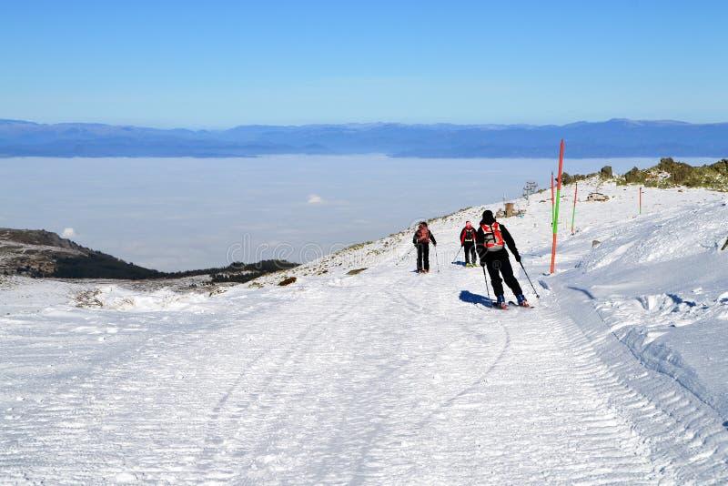Trois skieurs descendent de la crête photographie stock