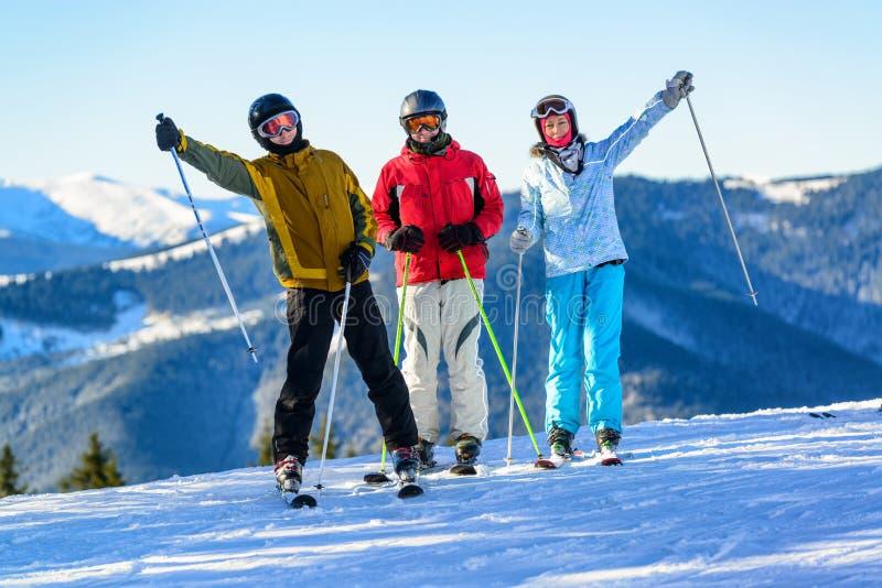 Trois skieurs heureux ayant l'amusement sur la pente de ski d'hiver photo libre de droits