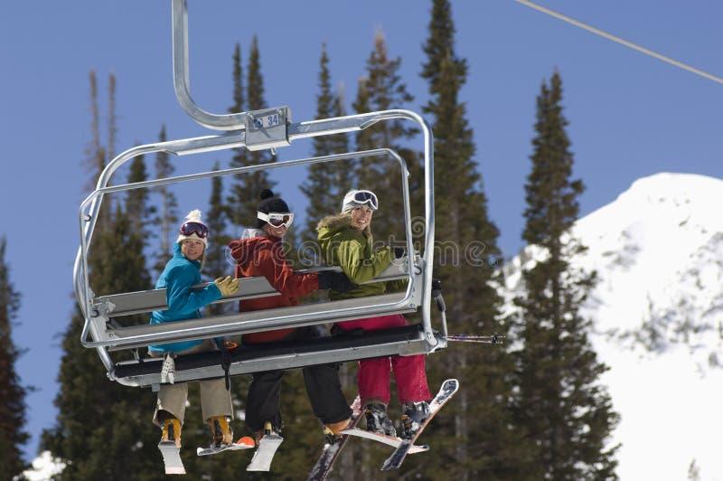 Trois skieurs sur l'ascenseur de chaise photographie stock libre de droits