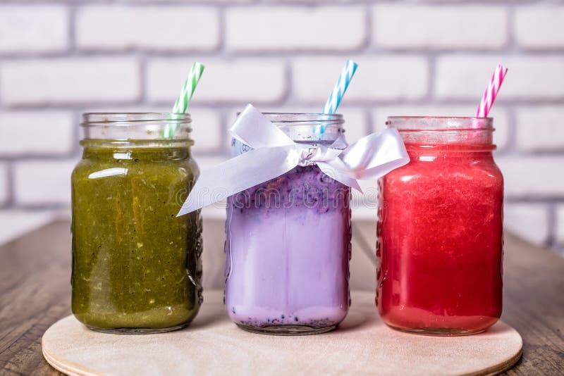 Trois smoothies sains frais savoureux ont servi dans des pots en verre avec la mangue et la framboise tropicale et le chou frisé  images stock