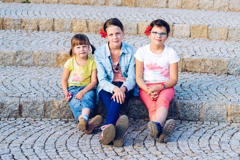 Trois soeurs s'asseyant sur les escaliers en pierre pendant des vacances d'été image libre de droits