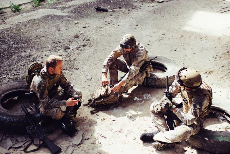 Trois soldats s'asseyent sur des pneus et ont le repos qu'ils ont eu un bon combat Les hommes veulent garder leur force pour le p photos stock