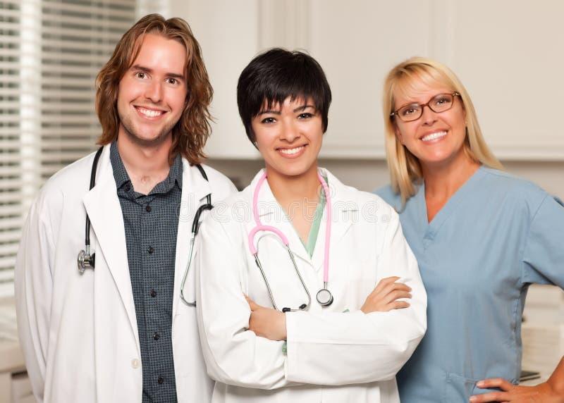 Trois souriant médecins ou infirmières mâles et féminins image stock