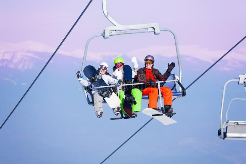 Trois surfeurs de sourire s'asseyant sur le ropeway image stock