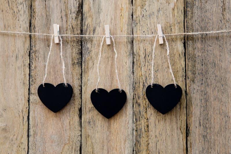 Trois tableaux noirs de forme de coeur accrochant sur la pince à linge sur ficelle AG photo libre de droits
