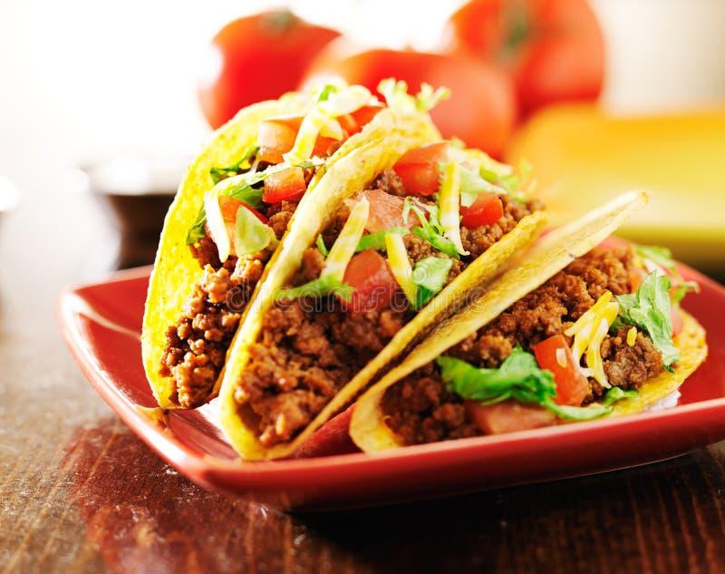 Trois tacos de boeuf avec du fromage, la laitue et des tomates image libre de droits
