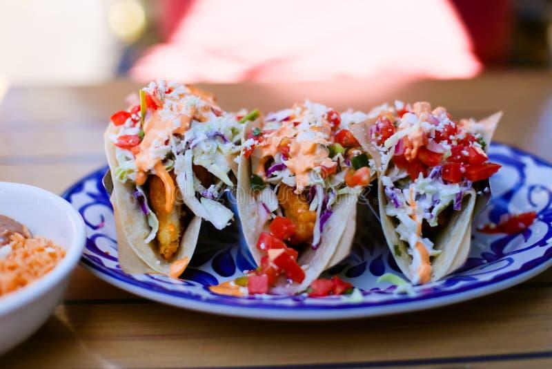 Trois tacos de poissons d'un plat bleu et blanc image stock