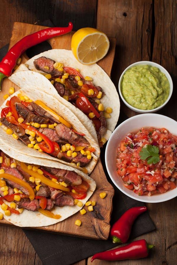 Trois tacos mexicains avec du boeuf marbré, Angus noir et légumes sur la vieille table rustique Plat mexicain avec le guacamole e photos stock