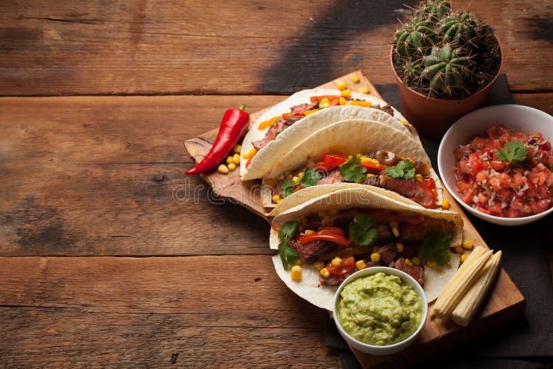 Trois tacos mexicains avec du boeuf marbré, Angus noir et légumes sur la vieille table rustique Plat mexicain avec le guacamole e images stock