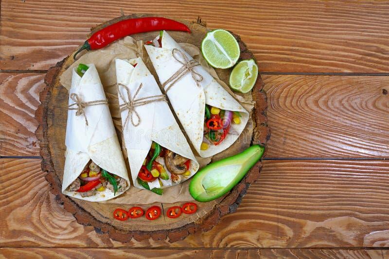 Trois tacos mexicains de carnitas de porc étendent à plat la composition sur un fond en bois images libres de droits