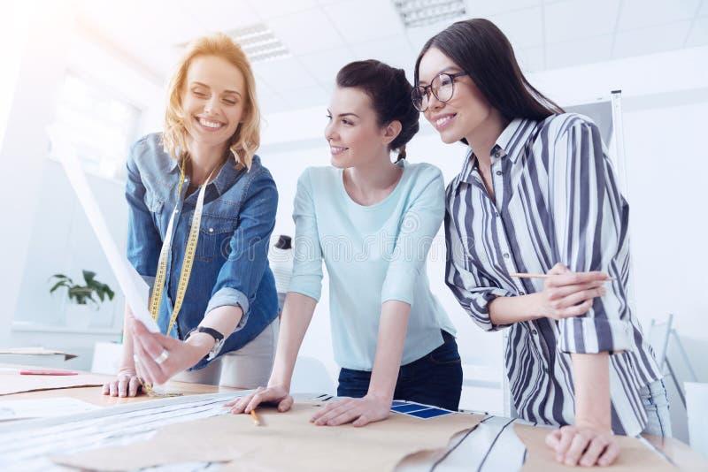 Trois tailleurs heureux travaillant avec les modèles de couture photo stock