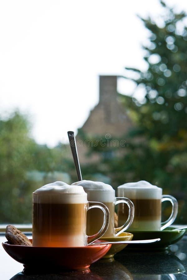 Trois tasses avec du café et la crème - verticale photos stock