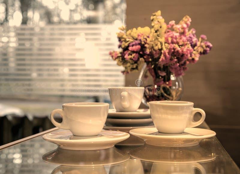 Trois tasses de café contre la fenêtre photo stock